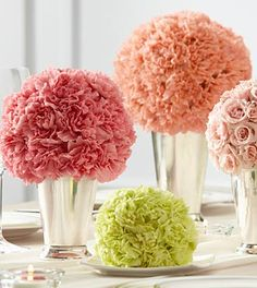 The Bridesmaid's Garden Centerpiece is a lovely way to bring bright, bold clusters of color to your reception. A collection of bouquets featuring a single type of flower, including peach carnations, pink carnations, pink spray roses, pistachio mini carnations, and green hydrangea are each set in small and medium silver julep cups to create a memorable display.