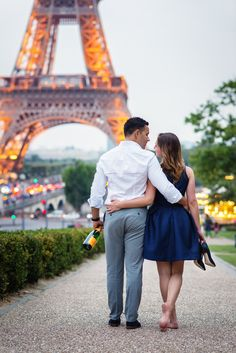 Let's find some beatiful place to get lost together.  Engagement picture in Paris of a couple walking in front of the Eiffel Tower with a champagne bottle and without shoes.