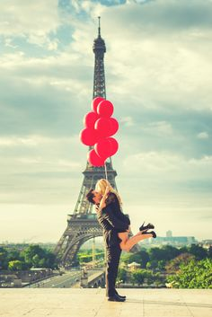Couple kissing in front of the Eiffel Tower with crazy red balloons. Engagement photo session in Paris