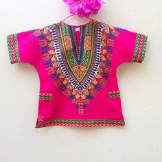 Tunic in a bright pink dashiki wax print with pop accent colors . Comfy loose shape, pockets at the sides.