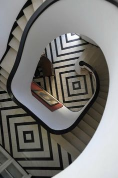 the diamond black and white pattern tiling is sophisticated combined with the shape of the staircase lends a design feel to the whole image