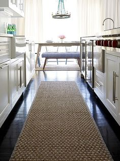 """""""I wanted to cut all the darkness of the floors,"""" Alex says, """"so we lined each area with sea-grass rugs—they are inexpensive and durable."""" And they feel good on the feet—especially in a place like the kitchen galley."""