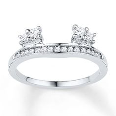 This exhilarating diamond enhancer ring adds shimmer with a row of diamonds along the band and clusters set to flank her diamond solitaire engagement ring (sold separately). Totaling 1/3 carat of dazzling diamonds, the enhancer is crafted in beautiful 10K white gold. Diamond Total Carat Weight may range from .29 - .36 carats.