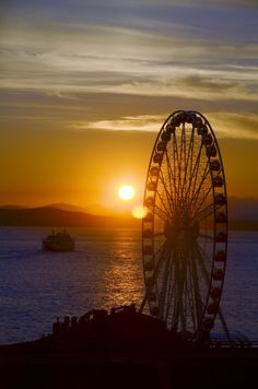Seattle Great Wheel by ctompsett - Seattle waterfront overlooking Elliott Bay towards the Olymipc Mountains, and ferry at sunset.