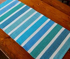 Overview: A gorgeous handwoven table runner or dresser scarf, in stripes of tropical blues and greens. Perfect for your lanai or sunroom, to bring sunshine to your day. Size: 34.5 inches by 15.5 inches. Style: Woven, by hand, in a striped weave structure. Perfect for a Florida