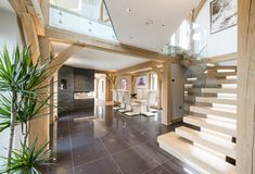 The contemporary staircase made from glazed balustrades and oak treads rises through a double-height space to the landing above. Building Design, Building A House, Oak Framed Buildings, Oak Frame House, Interior Design Inspiration, Interior Ideas, Floor Slab, Victorian Cottage, Energy Efficient Homes