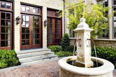 Three wood french doors with transom and 1' spacing.  Exterior view with fountain and herringbone patio.