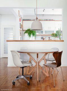 Sala de jantar integrada à cozinha. O morador optou pelo uso de cadeiras de diferentes modelos.