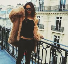 Carmel colored Fur Coat, Black Tank Top, Black Jeans, Black Nail Polish, Middie Ring, Multiple Rings, Curled Ombre Hair and Round Sunglasses.
