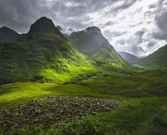 Photo by Ian Cameron. Glencoe, Highlands, Scotland. A shaft of sunlight breaks through low clouds around the Three Sisters on a spring afternoon and cuts a swathe of light across fresh new grass.