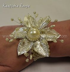 This stylish wrist corsage is handcrafted with Pearl Leaves, Pearls on wire with Diamante Pearl Brooch and created on a Pearl Bracelet. www.designelementflowers.com