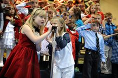 Second graders Natalie Dodson, 8, and Kensington Smith, 7, sing a duo as part of patriotic music performances Nov. 14 at Evans International Elementary School in Falcon School District 49. The school's students, families and faculty had gathered for a tribute to Veterans Day, which included lively musical presentations, an Army soldier's re-enlistment oath and a soldier's message from Afghanistan to his seven-year-old daughter.