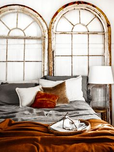 Beautiful bedroom with rust velvet cushion and terracotta throw styled bed with arch windows used as a bedhead. Terracotta is one of our top interior design trends for 2017 and used here it adds warmth and style to the bedroom for a unique and stylish home.