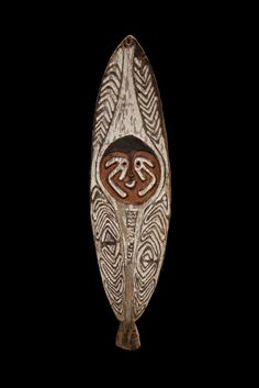 Gope board. The front design is classic for Urama Island/Purari Delta area with a central spirit face flanked by bands of repeating chevrons. The carving is done in high relief as with virtually all pre-1940 examples.
