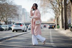 Pink duster coat over all-white outfit on the street at PFW // photo credit: The Styleograph
