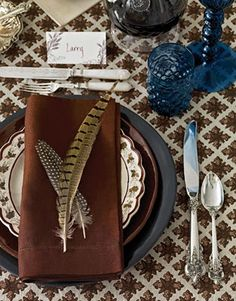 brown and white tablecloth, blue glassware, feather accents, autumn tablescape. Love this masculine look