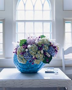 When a vessel is this distinctive, its form and color practically dictate what kinds of displays to create. This blue-glazed ceramic shell evokes summer at the beach, a time and place indelibly associated with billowing hydrangeas. Luxuriant cuttings from three cultivars, along with some leaves, supply the structure of this design. Airy pink gomphrena and white Cimicifuga cap the sea foam with spray.