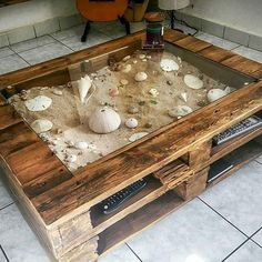 A DIY pallet wood glass display coffee table idea for the avid beachcomber! Leaves plenty of space to create a great beach scene with sand and shells. Featured on Completely Coastal.