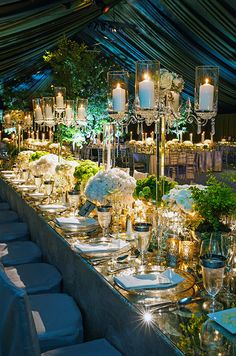 A glamorous banquet table is lined with glass candelabras and punctuated with various green and white blooms.