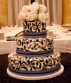 3 Tier fondant cake with handpainted black design with satin ribbon and fresh roses