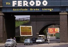 Cars passing under a railway bridge in London. The bridge carries an advertisement for Ferodo car brake linings, 1965.