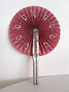 An exquisite handheld fan from the 1880's with hand painted flowers and a intricate metal handle. Perfect addition to any fan collection!   Measurement:  Closed: 8 3/4 inches long and 3/4 inch wide.  Open: 12 1/2 inches tall and 8 1/2 inches wide.