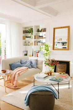 Salón muy luminoso con una librería, sofá, chimenea y alfombra, todo en blanco.  Mira sus ideas y las de otros salones este artículo.