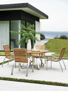 Tommy Bahama Teak Round Dining Table with Stainless Steel Accents.  Four Teak Dining Chairs.