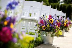 Yellow, Pink, Purple Wildflower Wedding Aisle Decor transition to center pieces. #weddingflowersfordecorations