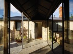 A glazed walkway cuts across a walled courtyard to link Stables Cottage to the main house.
