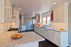 This remodeled kitchen was once dark and boring, but not anymore. Now, the homeowners can enjoy a timeless kitchen with a pop of color! The bold orange in the window frames and glass cabinets give this kitchen visual interest - without making it out of style.