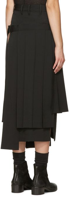 Mid-length wool skirt in black. Pleating throughout. Wrap-style overlay panel featuring cinch strap at side. Single-pocket styling. Offset vent at front and back hem. Asymmetric hem. Zip-fly. Unlined. Tonal stitching.