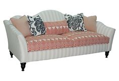 The sofa has flared arms and a camel back with masterfully carved legs. It is upholstered in beige and off-white with awning stripes for a chic, classic look. The contrast of the seat cushion and accent pillows add visual interest to the room. Includes five pillows as shown. One Kings Lane