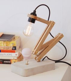 A beautiful desktop lamp with exposed bulb. Made with Swedish oak tree and concrete with brass details. Looks best with an Edison kind of bulb.