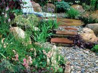 A soft pebble pathway is retained by using a brick edging for support. Soft surfacing for garden pathways consists of natural materials that include combinations of stone, wood and shell.