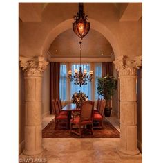 Very formal dining room flanked by Corinthian columns.  Beautiful chandeliers and custom detailing in the hallway.  Golf Estate Mansion for Sale in il Corsini | Mediterra | Naples, Florida