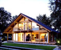 Casa de telhado de duas águas é feia? Este é exemplo de casa linda e moderna com um desenho bem simplista de telhado, que dá um charme todo especial lembrando muito um chalé. Fachada de vidro.