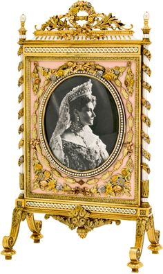 Fabergé photograph frame, workmaster Henrik Wigström, circa 1910. Inspired by a two-sided Louis XVI fire screen, one side contains a photograph of Tsar Nicholas II and the other of his Empress, Alexandra Feodorovna. This was a gift from the Tsar to his mother, the Dowager Empress Maria Fedorovna. The gold and platinum frame is enamelled white and seed pearls are set round the oval bezels. The whole is embellished with floral swags in multi-coloured gold.