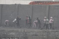 North Korean women work in a coal yard on the river bank as seen from across the border in China in Sinuiju, North Korea