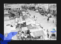 Mercado Terán, vista general sobre 5 de Mayo en la cual se observan, Puestos callejeros a las afueras del Mercado Terán, construidos con laminas, madera y cartón, también podemos observar negocios de la época y vehículos