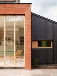 Architect Laura Dewe Mathews has added a staggered red brick extension to a house in West London with spaces for birdwatching, painting and gardening.