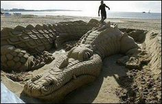 French artist Michael Klein puts the finishing touches to his sand sculpture, showing a Sea Dragon, on the beach of Cannes, southern France