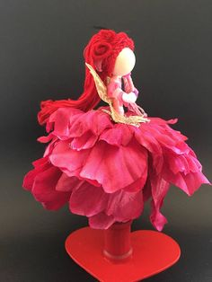 This all time beauty is dress in Red petal flowers and pink top with pink lace sleeves, Her skirt is top with gold embroidery threads, Her bright red hair is plaited in front and framed her face. she wears red felt flowers and black feathers. She carries a pink tassel Laurels to perform