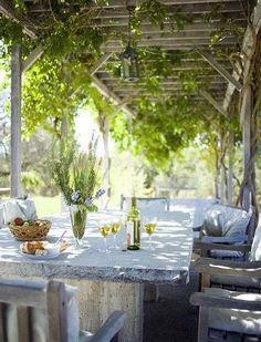 Outdoor dining in wisteria(?) draped arbor.