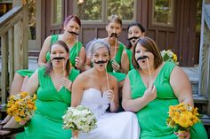 Bride with bridesmaids, mustache-on-a-stick photo shoot.