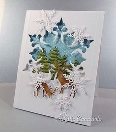 The negative space created by a large snowflake die makes a wonderful window for this snowy forest scenery.  You could create a similar window using any shape.  This one uses fir trees, deer and snowflakes along with a starry-dot sky.  DIY Christmas card.