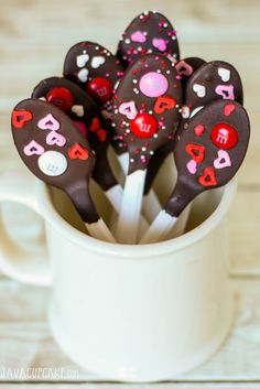 Valentine's Day treats don't have to be difficult to make!  Chocolate dipped spoons & cookies decorated in red & pink are simply perfect!  Valentine Chocolate Dipped Cookies & Spoons | JavaCupcake.com