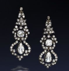 A pair of diamond pendent earrings, last quarter of the 19th century  Each foliate surmount suspending a collet-set cushion-shaped diamond and a further pear-shaped diamond central drop, within an openwork scrolling surround, set throughout with old brilliant-cut and cushion-shaped diamonds, mounted in silver and gold, diamonds approximately 9.20 carats total, later screw fittings, length 5.5cm