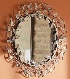 Longaberger Bronze Leaf Wall Mirror. This beautiful Bronze Leaf Mirror was inspired by an antique garden gate and will bring a hint of nature into your home. The wrought iron finish is black with hand painted bronze highlights that accentuate the leaf design elements.
