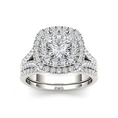 On the day you ask for her hand, wow her with this stunning engagement ring crafted in white gold. Featuring a brilliant diamond center stone, it is surrounded by a double frame of smaller accent diamonds atop a diamond-lined shank.